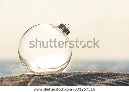 Christmas-tree decoration glass ball at ocean beach sunset time - xmas and New Year's vacation in hot countries concept - stock photo
