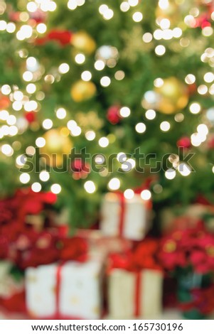 Christmas Tree Decoration with Ornaments Lights Poinsettia and Presents Bokeh Blurred Defocused Background - stock photo