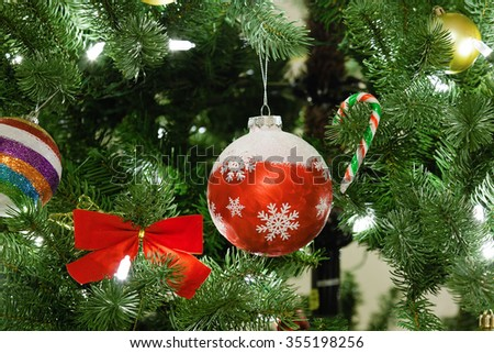 Christmas tree decorations closeup. Selective focus on glass red ball. - stock photo
