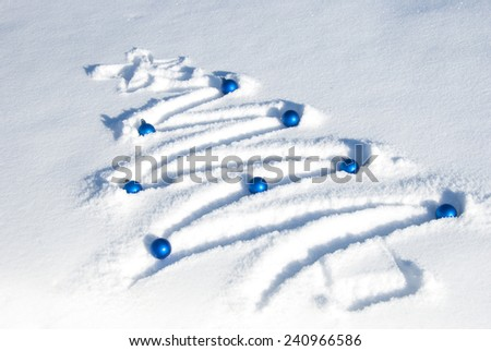 Christmas tree drawn in the snow and adorned with blue ornaments - stock photo