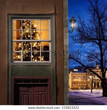Christmas tree home seen from outside in a snowy little winter town - stock photo