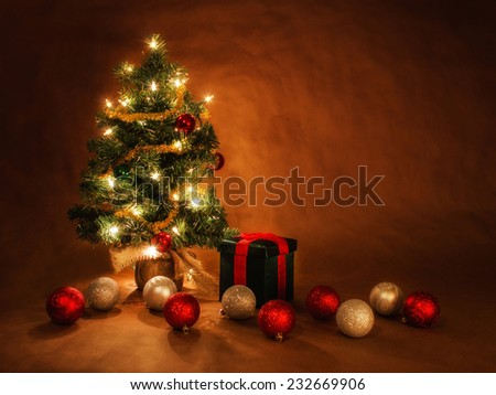 christmas tree illuminated with holiday decor with a glamour glow overlay effect - stock photo