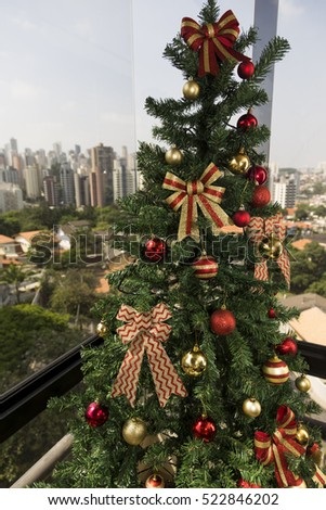 Christmas tree in daylight, with a city landscape in the background