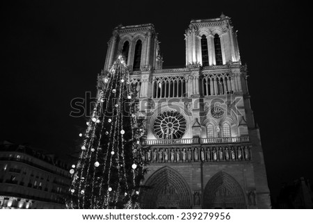 Christmas tree in front of the Notre Dame cathedral in the evening. Paris, France. Aged photo. Black and white. - stock photo