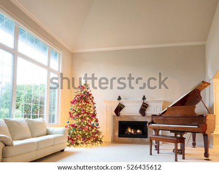 Christmas tree in living room with burning fireplace and grand piano during bright day time.