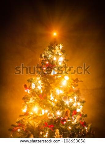 Christmas Tree lit on brown wallpaper - stock photo