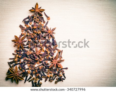 Christmas tree made from brown spices anise stars and cloves on burlap background - stock photo