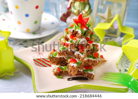 christmas tree made from stack of star shape dark bread with cheese,chive and red pepper for breakfast - stock photo