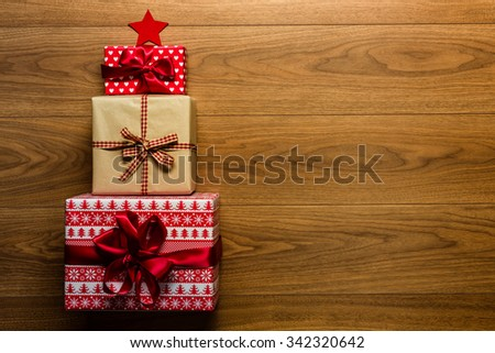 Christmas tree made of beautifuly wrapped presents on wooden background, view from above - stock photo