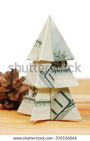 Christmas tree made of hundred dollar bills on a wooden board with a bump on a white background - stock photo