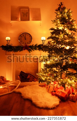 Christmas tree near fireplace in room - stock photo