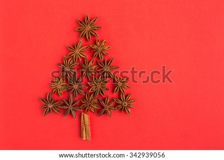 Christmas tree of cinnamon sticks and star anise on re background - stock photo