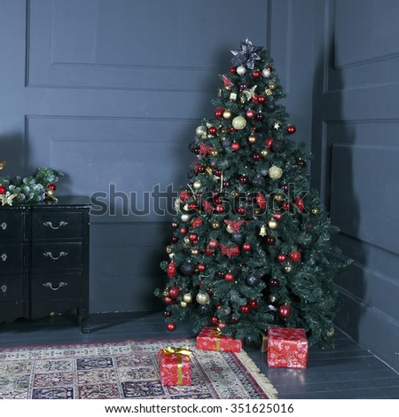 Christmas tree on wooden floor in white interiour. Christmas tree decorates with artificial flowers, garlands and Christmas toys - stock photo