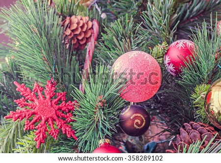 Christmas tree red ornaments, globe hanging, snow flake, green tree, firs with cones, close up. - stock photo