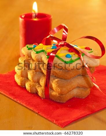 Christmas tree shaped cookies in a stack, tied with a red ribbon with a candle on background - stock photo