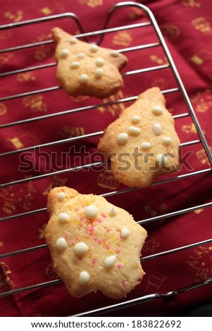 Christmas tree shaped cookies on a cooling rack. - stock photo