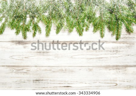 Christmas tree sprigs with snow over bright wooden background.  - stock photo