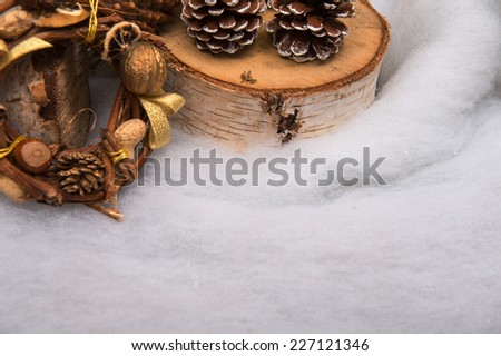 Christmas tree toys  and decoration like  fir branch and box with candle wooden log and pine and fir cones  and wreath of nuts hazel  peanuts  on snow with  copy place - stock photo