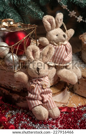 Christmas tree toys  like  plush rabbits  and wooden  box  and snowflakes near  fir with selective focus  - stock photo