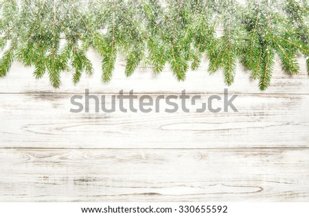 Christmas tree twigs with snow on wooden background - stock photo