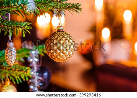 Christmas tree with a golden bauble and candlelights - stock photo