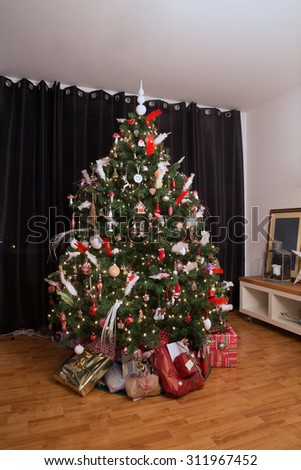 christmas tree with christmas presents under it in a real living room