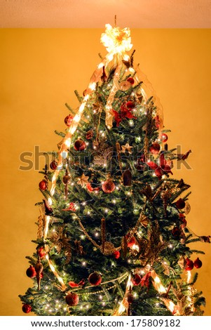 Christmas tree with decorations and lights on wall background - stock photo