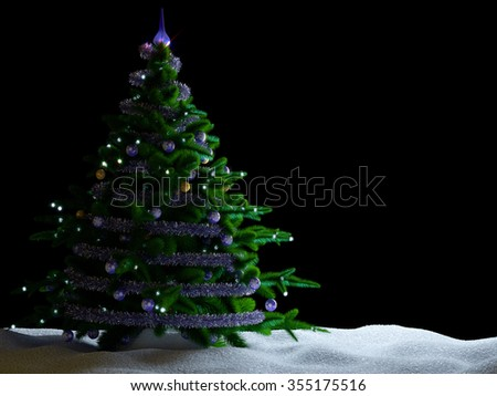 Christmas tree with decorations and snow on isolate black background. - stock photo
