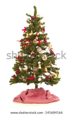 Christmas Tree with Festive Decorations, antique and new,  on white background with a red and white tree skirt - stock photo