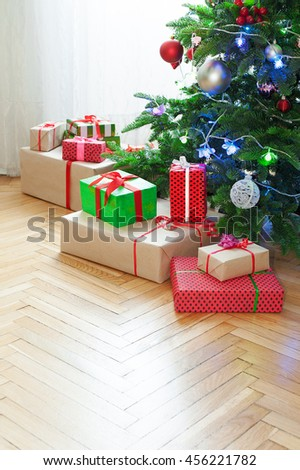 Christmas tree with festive gifts at home - stock photo