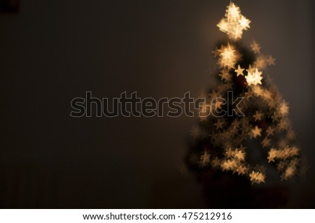 Christmas tree with fiber optic lights. Bokeh is star-shaped. Background for christmas card