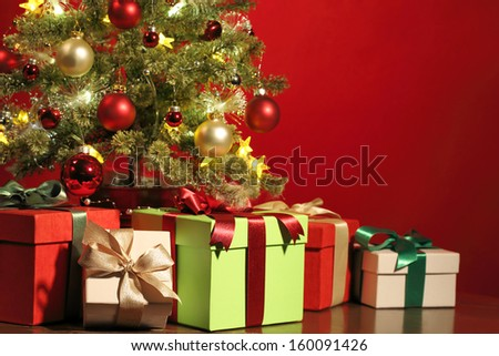 Christmas tree with gifts on red background. - stock photo