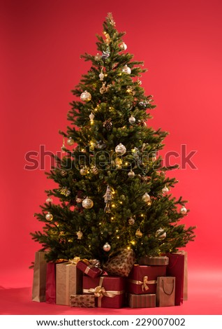 Christmas tree with gifts on red background full length - stock photo