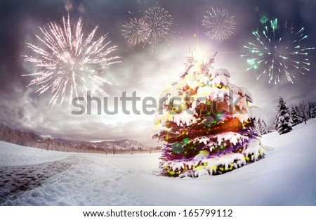 Christmas tree with lightings in the forest at dramatic sky with fireworks - stock photo
