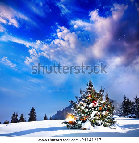 Christmas tree with lights in mountain snow forest at dramatic evening background - stock photo