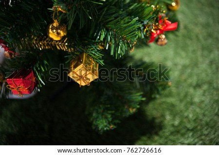 christmas tree with little gift,golden and red gift hang on chrismas tree,christmas tree with decorative on grass background,selective focus