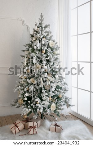 Christmas tree with presents underneath in living room - stock photo