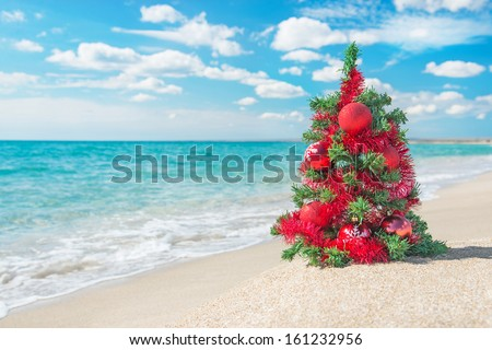Christmas tree with red decorations on the sea beach. Christmas vacation concept. - stock photo