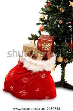 christmas tree with sack full of gifts over white - stock photo