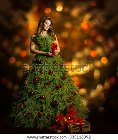 Christmas Tree Woman Fashion Dress, Model Girl and Candle, Present Gift on Xmas Red Lights Background - stock photo