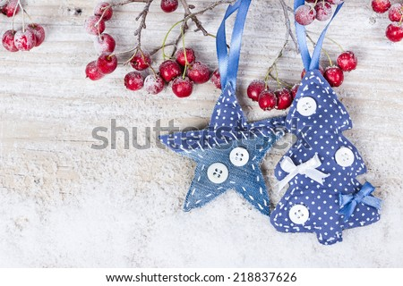Christmas trees and stars on a branch with berries on wooden background