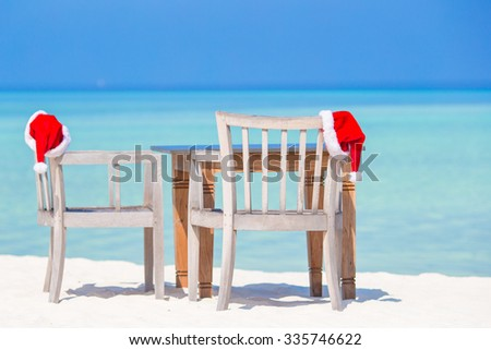 Christmas tropical concept: beach cafe with red Santa Hats  - stock photo