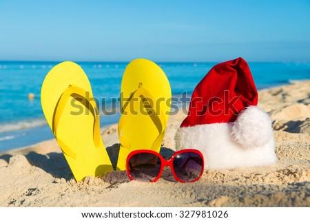 Christmas vacation at sea. Happy  New Year holidays. Santa hat, sandals, sunglasses on sandy beach - stock photo