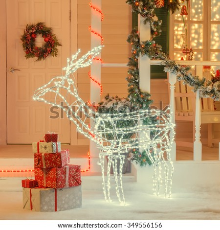 Christmas vintage house decorated with beautiful illuminated deer, lights and gift boxes on snow - stock photo