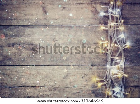 Christmas warm gold garland lights on wooden rustic background. filtered image with glitter overlay  - stock photo