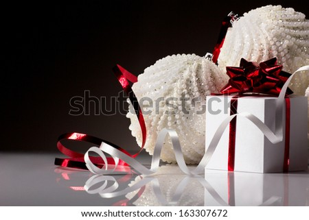 christmas white  ball and gift red box with bow on dark grey background - stock photo