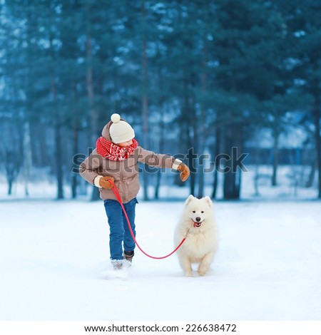 Christmas, winter and people concept - happy teenager boy running and playing with white Samoyed dog outdoors in winter day - stock photo