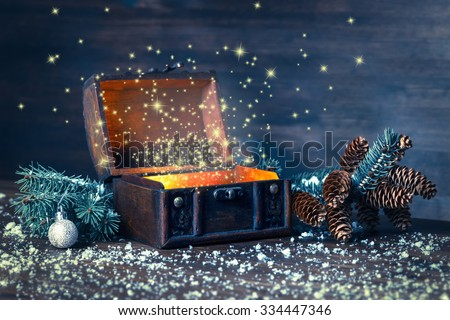 Christmas winter fairy with miracle in opened chest. Background of mystery gift New Year, fir tree and snow. Instagram style  - stock photo