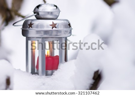 Christmas winter holiday background. Burning candle in the lantern in snow - stock photo