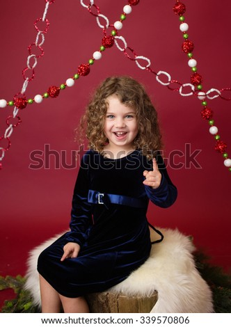 Christmas, Winter Holiday themed setup: beautiful child ornaments and decorations on red background, sitting on tree stump with branches - stock photo